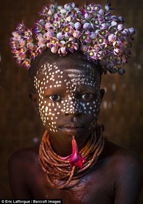 Một cô bé trang trí hoa trên đầu. Cô gái thuộc một bộ tộc ở Korcho, thung lũng Omo, Ethiopia.