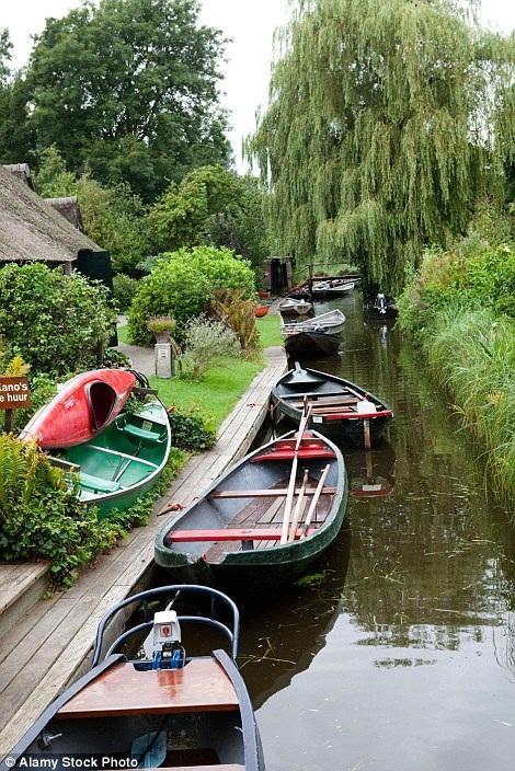 Thuyền gỗ nối đuôi nhau dọc theo dòng kênh xanh
