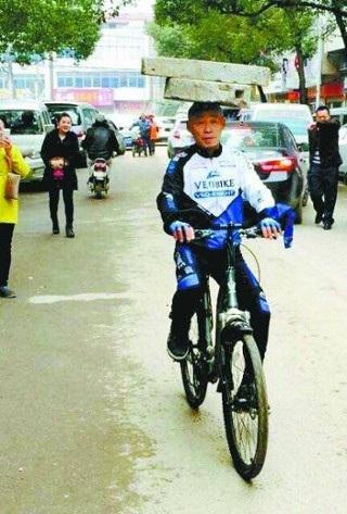 Trong khi đó, một người đàn ông 52 tuổi khác đến từ Vũ Hán, lại thể hiện khả năng cân bằng của mình, khi đầu đội khối đá và lái xe đạp.
