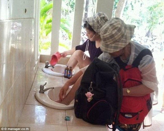 Du khách Trung Quốc cho chân vào bồn rửa mặt trong một điểm du lịch ở Thái Lan