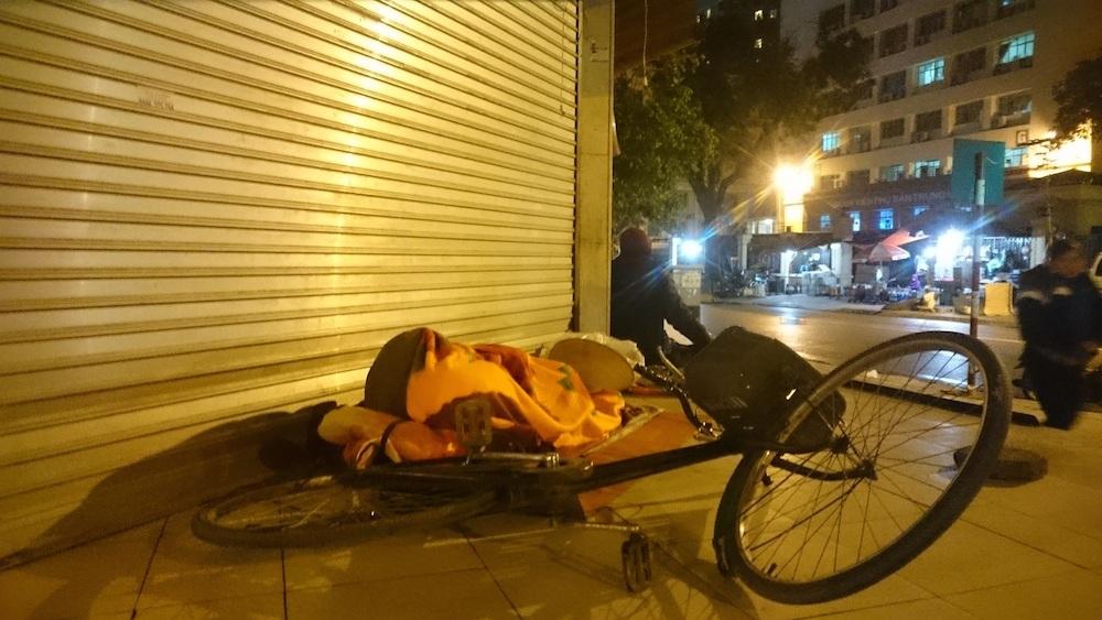 Một người vô gia cư ngủ trên vỉa hè, chiếc xe đạp là tài sản duy nhất để giúp họ mưu sinh. Ngay cả khi ngủ cũng nằm bên cạnh.