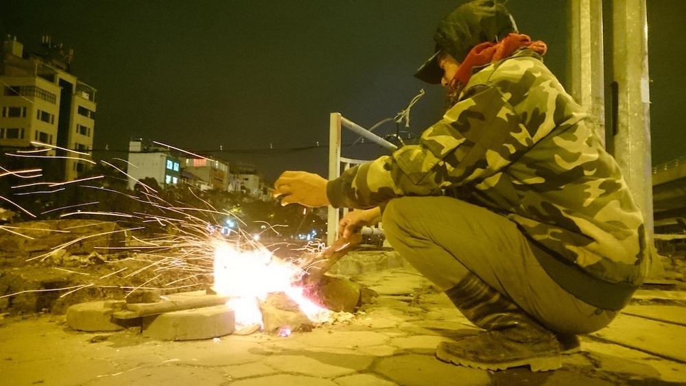 Những người hành nghề xe ôm thì chọn cách đốt lửa để giữ ấm cho mình.