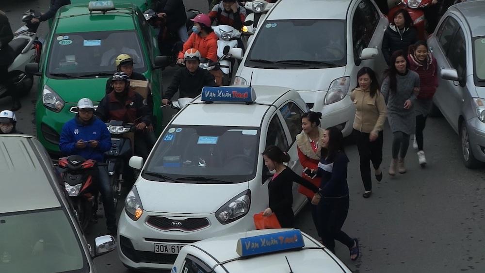 Hàng chục người nắm tay nhau để sang đường trong lúc giao thông bị tắc nghẽn. Cách đó không xa có một cầu vượt dành cho người đi bộ nhưng họ đã phớt lờ.