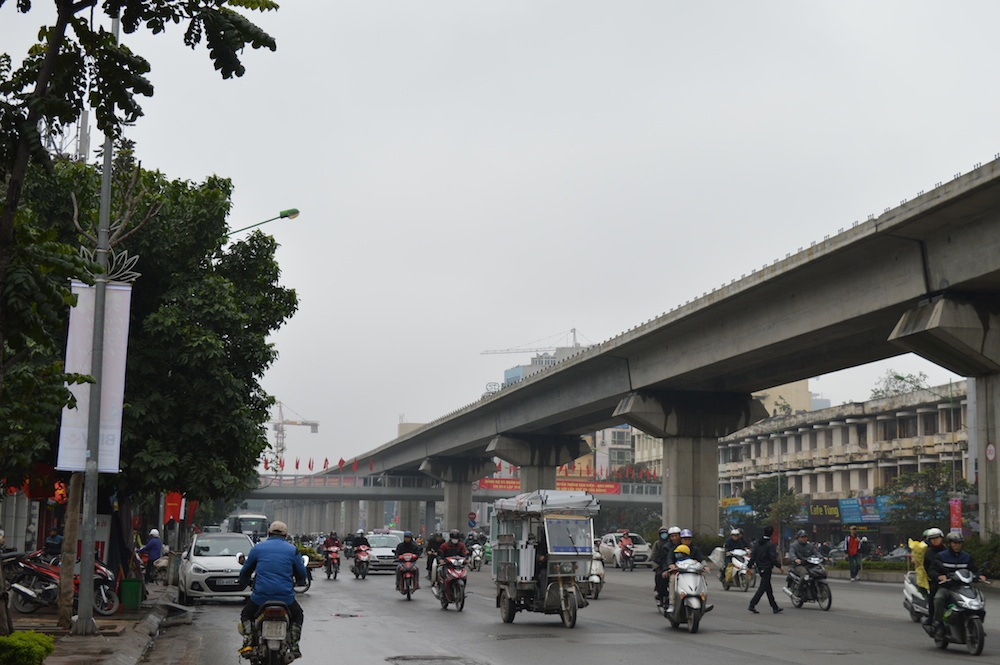 Một người đàn ông đi bộ sang đường trong khi đó cầu vượt chỉ cách vài chục m.