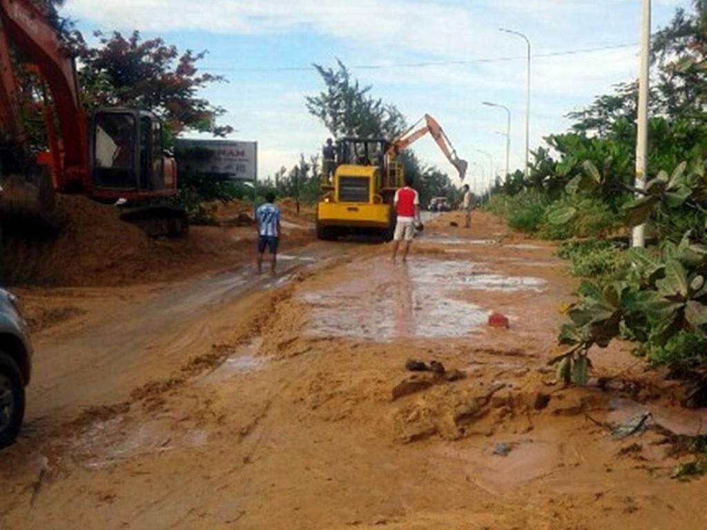 Lượng bùn khá lớn từ vụ vỡ đê tràn ra đường khiến giao thông tê liệt sáng 16/6 (ảnh: Trúc Hà)