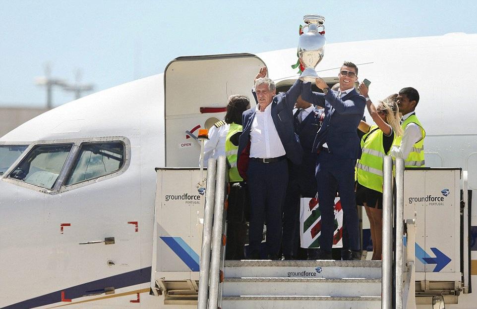 HLV Fernando Santos và đội trưởng Ronaldo là những người bước ra cửa máy bay đầu tiên, nâng cao cúp vô địch