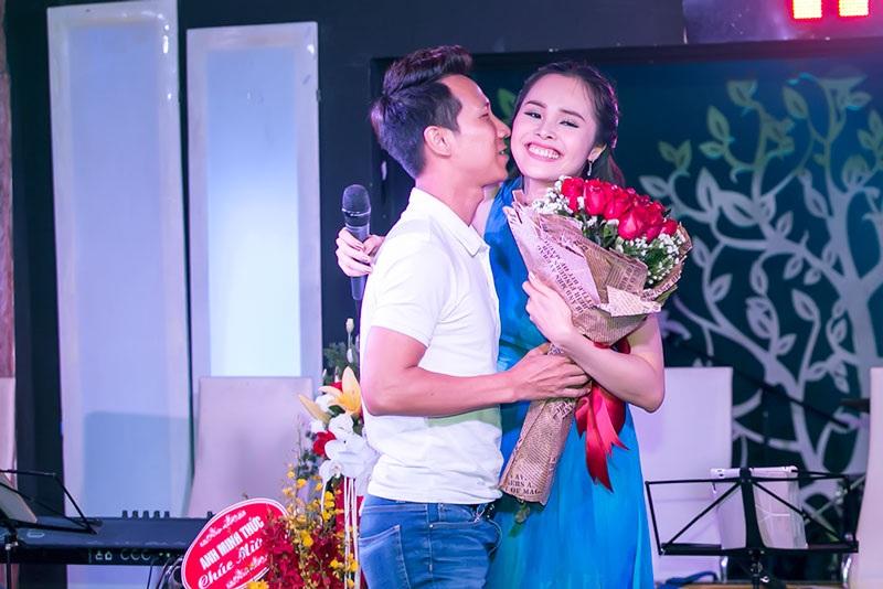 Ca sĩ Lê Anh Dũng ngồi chăm chú nghe bà xã hát. Nam ca sĩ chuẩn bị một bó hoa hồng lên tặng và hôn vợ ngay trên sân khấu trong tiếng vỗ tay của khán giả.