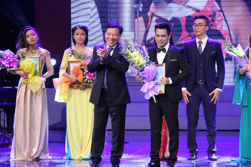 Ông Tô Văn Động, Giám đốc Sở Văn hóa và Thể thao Hà Nội trao giải cho thí sinh tại cuộc thi Giọng hát hay Hà Nội 2014