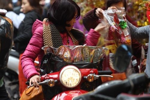 Mặc dù công việc cuối năm khá bận rộn, nhưng người phụ nữ này vẫn tranh thủ tạt qua phố Hàng Mã để mua bộ mũ áo cho ông Công, ông Táo nhà mình.