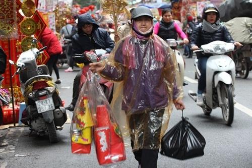 Ngay từ 8 giờ sáng, bất chấp mưa rét bởi đợt gió mùa mới đang tràn về, người dân Hà Nội vẫn mặc áo mưa xuống phố sắm sửa lễ cúng ông Công, ông Táo cho gia đình mình.