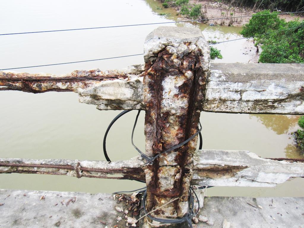 Lan can của cầu bị ăn mòn nặng, trơ cả lõi sắt hoen gỉ.