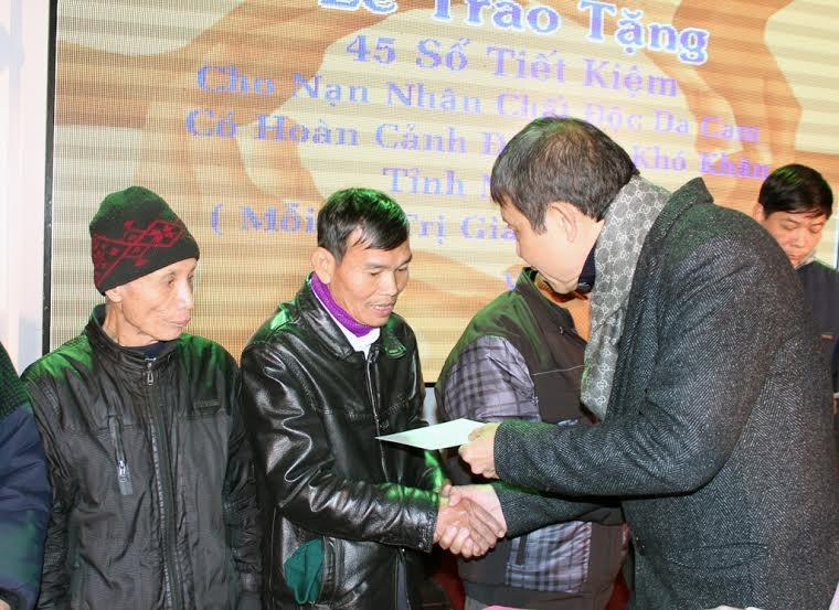Ông Minh Hồng trao sổ tiết kiệm cho các gia đình bị chất độc da cam.