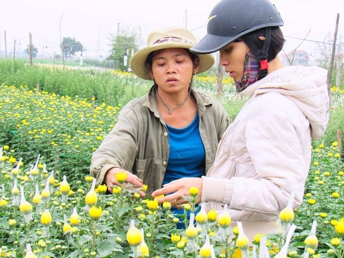 Chị Tuyết giới thiệu tỉ mỉ những đặc tính của hoa cho khách hàng bằng kinh nghiệm trồng hoa lâu năm của mình.