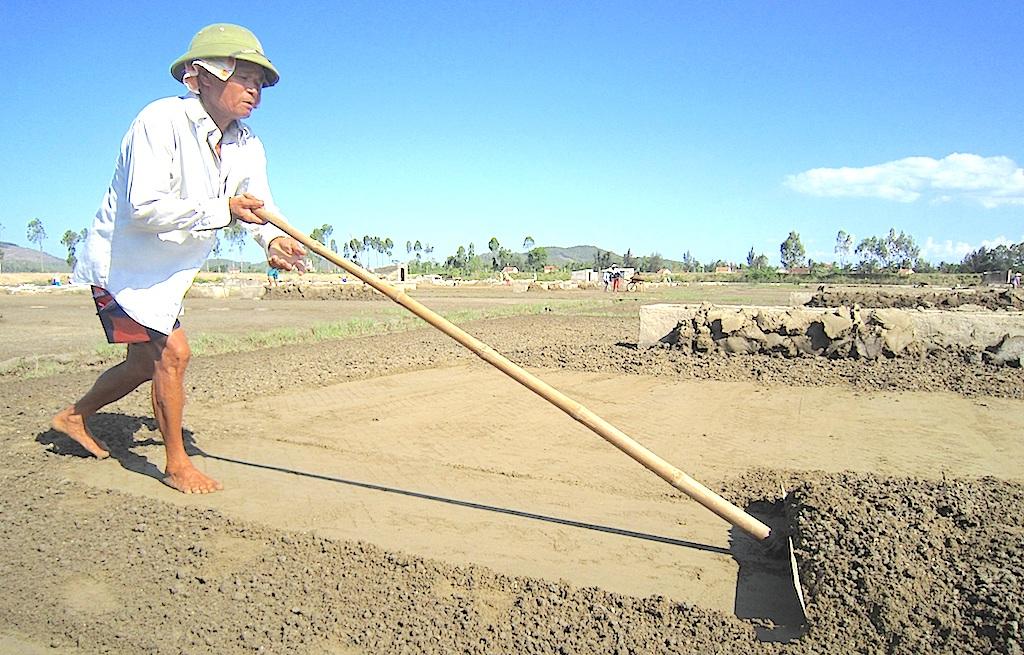 Phụ nữ, trẻ em, người già cày giữa trời nắng công đoạn làm đất để mong có được những hạt muối tinh trong.