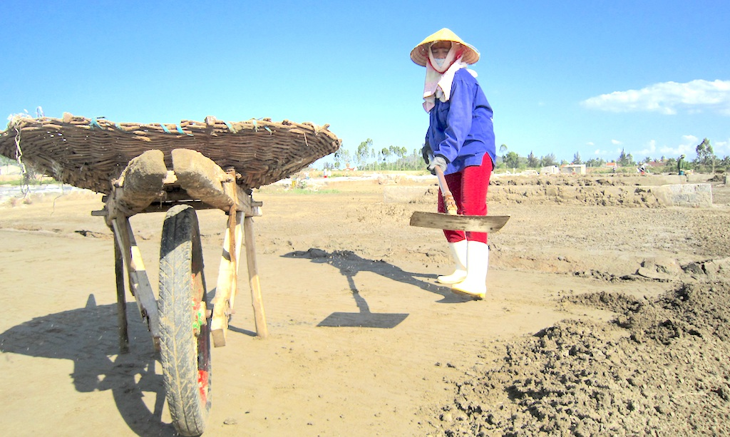 Chị Bùi Thị Thư (48 tuổi, xóm Tân Thắng, xã An Hòa) đang vất vả xúc cát được ngâm nước biển đem phơi đổ vào mương.