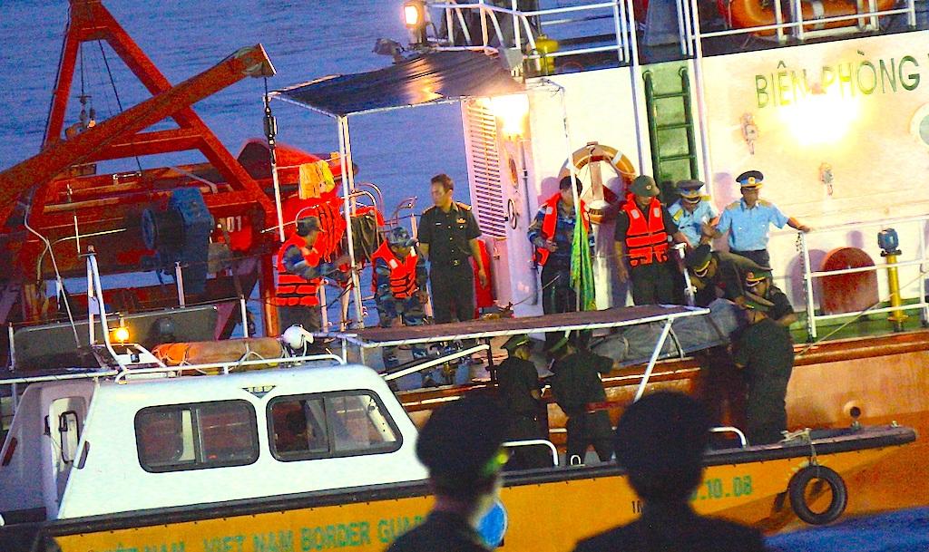 Thi thể phi công Khải được đưa xuống một ca nô và chuyển vào cầu cảng.