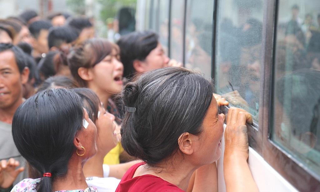 Nhiều người đã vây kín xe, khóc lóc khi nhìn qua tấm kính xe ...