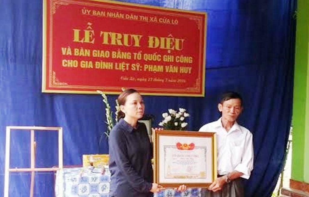 Bà Nguyễn Thị Dung - Phó chủ tịch UBND thị xã Cửa Lò trao Bằng Tổ quốc ghi công cho thân nhân liệt sỹ Phạm Văn Huy.