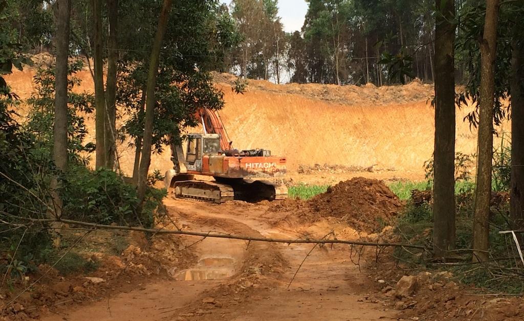 Chiếc máy múc đang hoạt động đào đất.