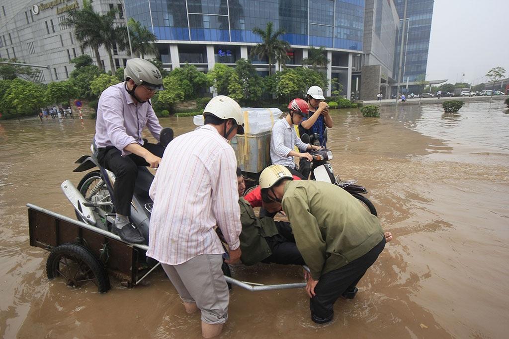 Cơn mưa lớn khiến giao thông thủ đô tê liệt cục bộ ở một số điểm sáng 25/5. Nhiều nơi bị ngập nặng. Tiêu biểu là khu vực tòa nhà Keangnam, người dân phải nhờ tới... xe bò để thoát lụt.