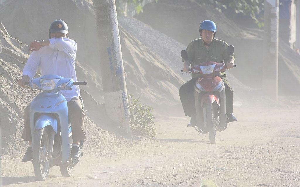 Những người đi xe máy không mang khẩu trang phải dùng tay che miệng, mũi để hạn chế hít phải khí bụi.