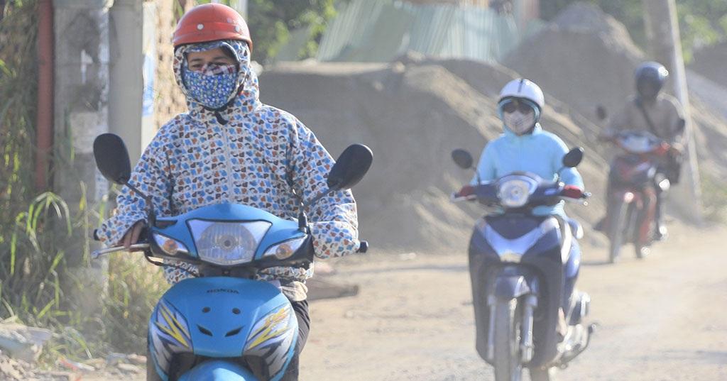 Vì đường quá bụi, có người đi xe máy qua đây phải dùng tới hai chiếc khẩu trang.