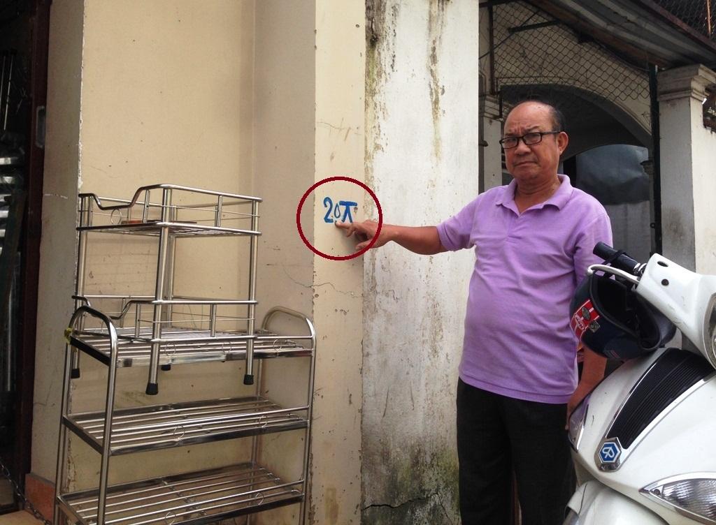 Ông Vương Mạnh Hùng chỉ vào dấu mốc mới sau khi giảm 0,7 m và cho rằng vẫn còn quá cao, nhà ông cũng như nhiều nhà dân khác sẽ biến thành hầm