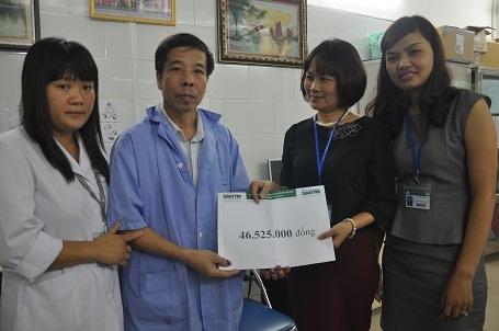 Gia đình bác Tuất nhận quà bạn đọc Dân trí trước sự chứng kiến của bác sĩ Phạm Thị Bích Mận - Trưởng phòng Công tác xã hội bệnh viện và bác sĩ Đoàn Thu Trà - Phó trưởng khoa Truyền nhiễm.