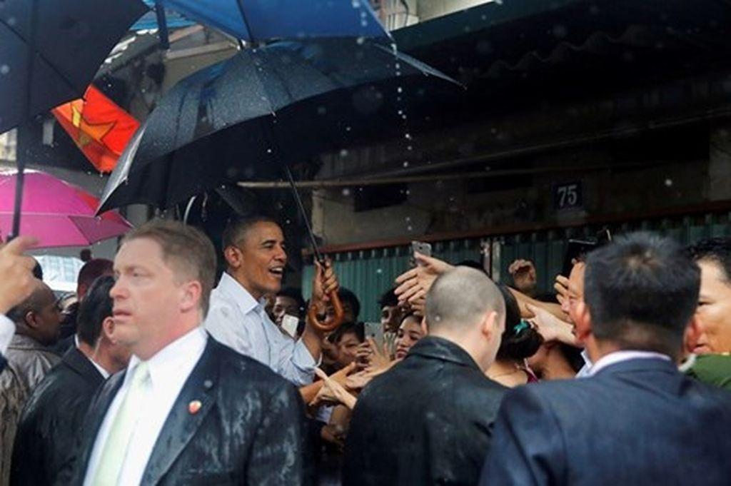 Trước khi rời Hà Nội vào TPHCM, Tổng thống Obama đã ghé thăm làng Mễ Trì Hạ. Dù trời bất chợt đổ mưa nhưng ông vẫn rất vui vẻ bắt tay, trò chuyện với người dân địa phương (Ảnh: Reuters)