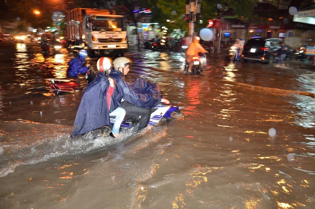 Cơn mưa như trút nước kéo dài khoảng 4 tiếng đồng hồ khiến nhiều tuyến đường ở TPHCM ngập sâu trong nước, xe chết la liệt, người dân phải bì bõm lội nước, dẫn bộ xe trên đường... (Ảnh: Đình Thảo)