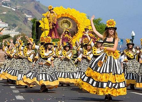 Vũ công diện trang phục đính hoa rực rỡ vừa diễu hành vừa nhảy múa trên đường phố