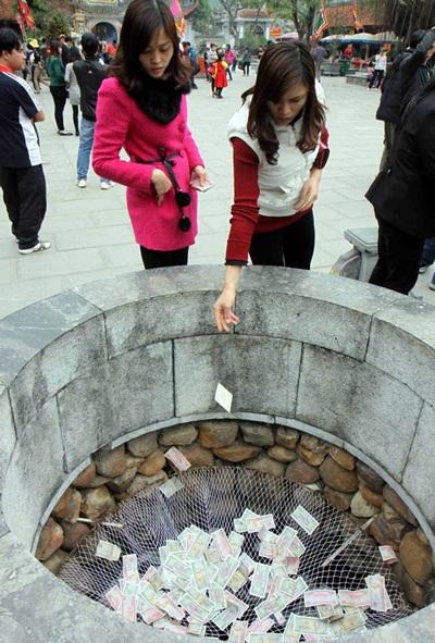 Du khách đua nhau đặt tiền lẻ tại lễ hội Chí Linh (Hải Dương). Ảnh TTXVN