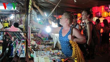 Du khách lựa chọn những đồ vật được bày bán tại chợ đêm ở Hội An. (ảnh: Trà Xanh)