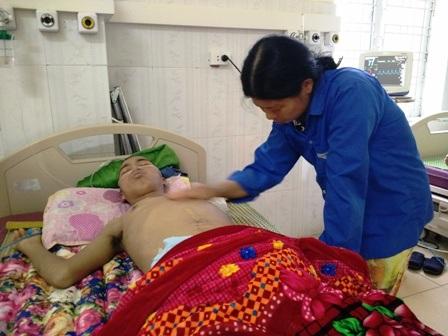 Chị Huấn chỉ biết đứng bên người con trai nằm bất tỉnh cầu mong một phép màu đến với gia đình mình