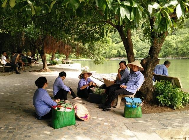 Chờ khách dưới cái nắng gay gắt, họ phải ngồi dưới bóng cây tránh nóng