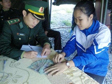 Em Lê Thị Phương Ly đang bàn giao số tiền 18 triệu đồng cho Đồn Biên phòng Roòn
