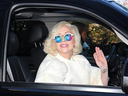 Nữ ca sĩ nổi tiếng vẫy tay chào người hâm mộ đang đứng bên ngoài khách sạn để chờ đón cô.