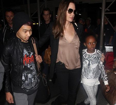 Angelina ômcô con gái nuôi Zahara trước rừng người hâm mộ.