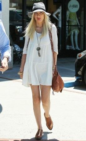 Taylor Swift thật năng động, trẻ trung chỉ với áo phông kẻ ngang và quần ống côn màu nâu đỏ.
