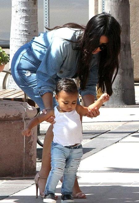 Bé North mới chập chững biết đi nên cô bé rất thích được mẹ dắt tay