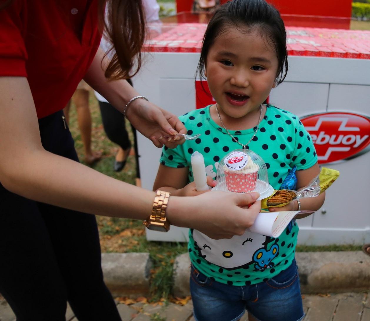 Một cô bé háo hức nhận bánh từ chương trình