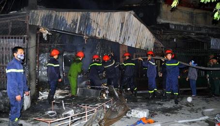 Lực lượng cứu hỏa phá tường rào để dập lửa.