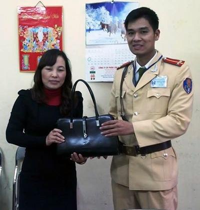 Trung úy Thành trao trả chiếc túi có nhiều tài sản giá trị cho chị Huyền.