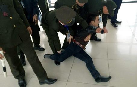 Nam thanh niên lăn ra sàn khi lực lượng an ninh tiếp cận. (Ảnh: otofun)