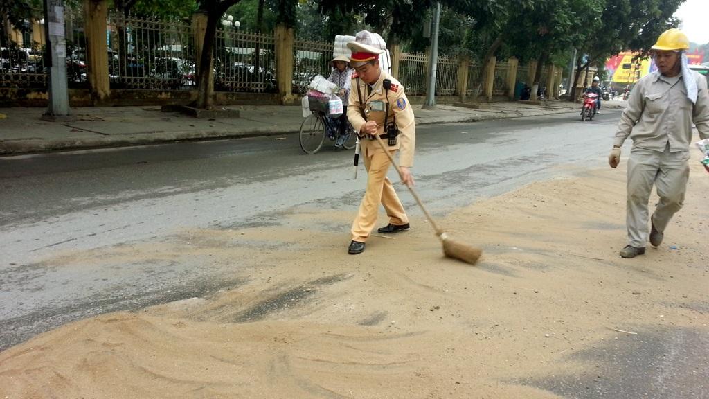 Rải cát làm sạch dầu trên mặt đường.
