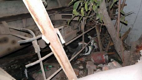 Một chiếc xe máy nát bét dưới gầm xe chở rác.
