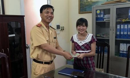 Thượng úy Phạm Ngọc Thành (Phó Đội trưởng Đội CSGT số 7) trao trả tài sản cho chị Nguyễn Minh Thu.