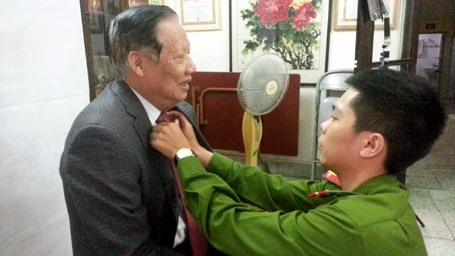 Chỉnh sửa trang phục trước khi chụp ảnh cho cụ Lê Huy Ngọ, nguyên Bộ trưởng Bộ NN&PTNT.