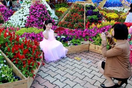 Rất nhiều em nhỏ được bố mẹ dẫn đi dạo con đường hoa Xuân và chụp hình lưu niệm