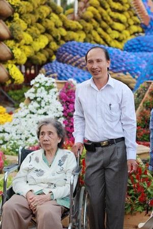 Một cụ bà dù đi xe lăn cũng ra chụp hình chung với con đường hoa Xuân